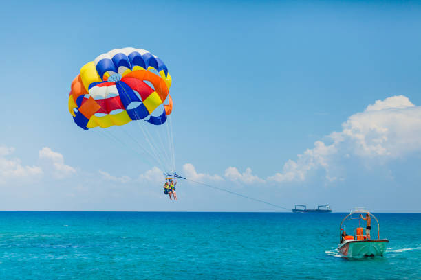 Couple of tourists flying on a colorful parachute stock photo