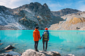 istock Couple of tourists looks at the lake. Honeymoon in Alps. Beautiful turquoise lake in the mountains. 860578772