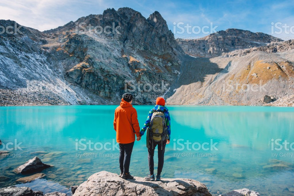 Couple of tourists looks at the lake. Honeymoon in Alps. Beautiful turquoise lake in the mountains. stock photo