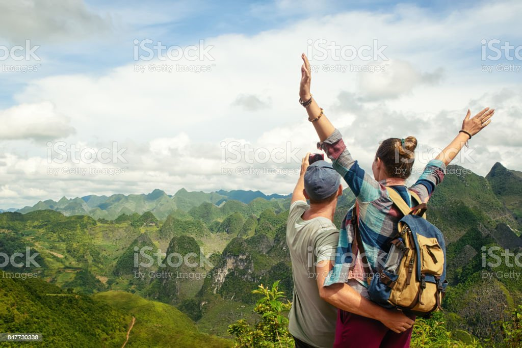 couple of tourists making selfie on background of karst mountains. stock photo