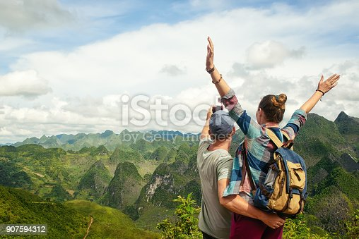 istock couple of tourists making selfie on background of karst mountains. 907594312