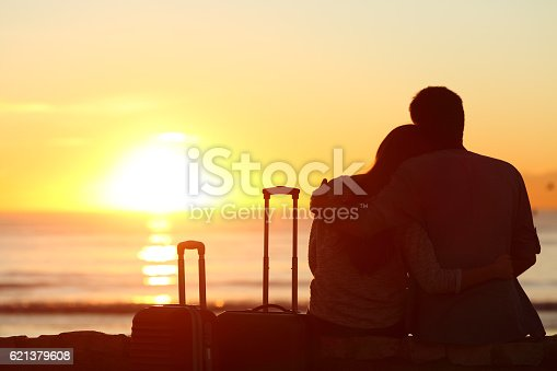istock Couple of tourists on vacations watching sun 621379608