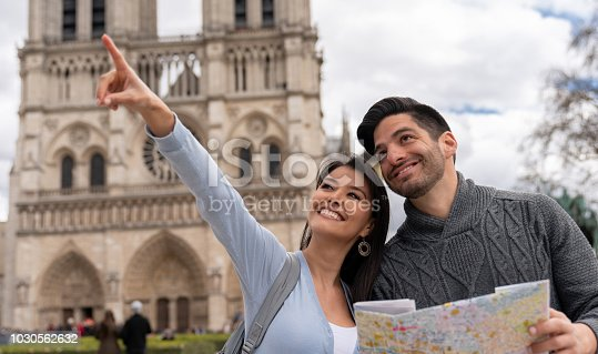 Portrait of a loving couple sightseeing in Paris vising Notre-Dame and using a map while pointing away