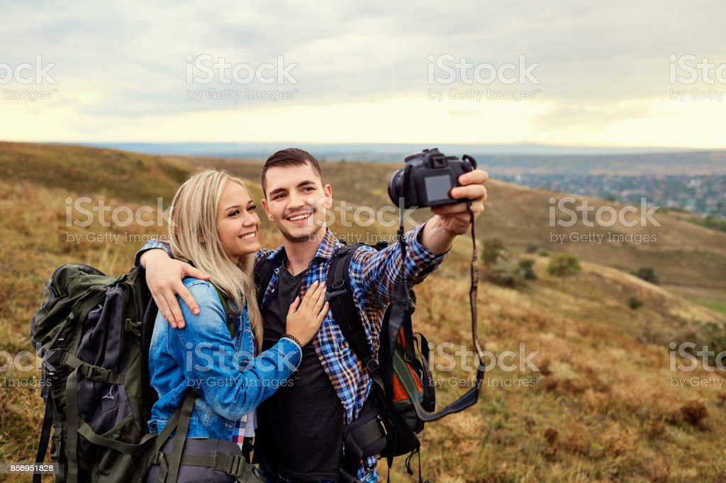 Couple of travelers are photographed on a camera in nature. stock photo