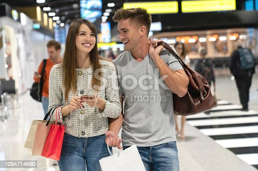 Couple of travelers walking at the airport and looking very happy shopping at the duty free and holding bags