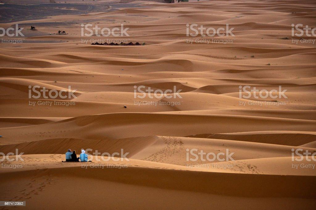 Un couple de touristes occidentaux par le guide berbère en attendant le lever du soleil matin - Photo
