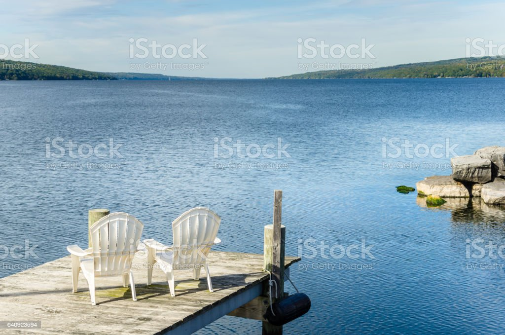 Couple of White Chairs Facing a Lake stock photo