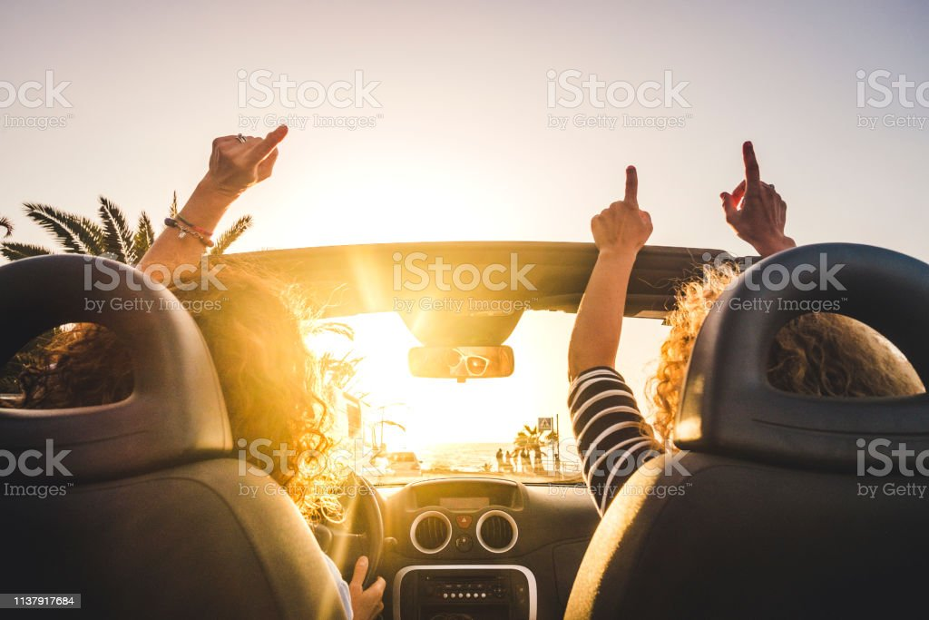 Couple of woman friends traveling and driving having a lot of fun dancing in the car with opened roof and summer vacation sunset ocean in front - concept of friendship together and nice lifestyle for independent girls Couple of woman friends traveling and driving having a lot of fun dancing in the car with opened roof and summer vacation sunset ocean in front - concept of friendship together and nice lifestyle for independent girls Car Stock Photo