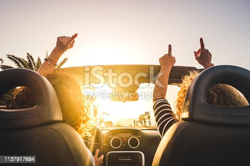 istock Couple of woman friends traveling and driving having a lot of fun dancing in the car with opened roof and summer vacation sunset ocean in front - concept of friendship together and nice lifestyle for independent girls 1137917684