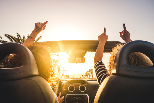 Couple of woman friends traveling and driving having a lot of fun dancing in the car with opened roof and summer vacation sunset ocean in front - concept of friendship together and nice lifestyle for independent girls