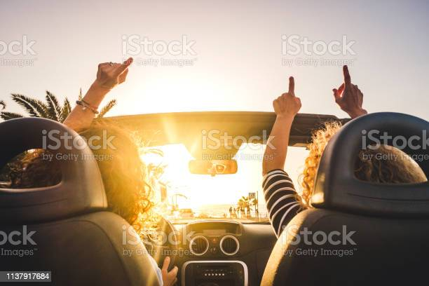 Couple Of Woman Friends Traveling And Driving Having A Lot Of Fun Dancing In The Car With Opened Roof And Summer Vacation Sunset Ocean In Front Concept Of Friendship Together And Nice Lifestyle For Independent Girls Stock Photo - Download Image Now