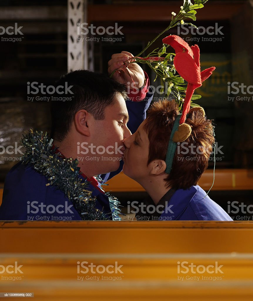 Couple of workers holding mistletoe above heads kissing in warehouse aisle, side view royalty-free stock photo