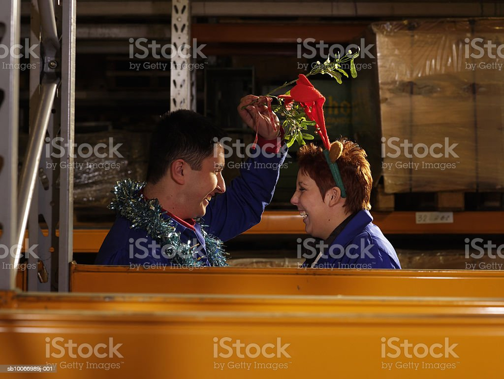 Couple of workers holding mistletoe above heads standing face to face in warehouse aisle, side view royalty-free stock photo