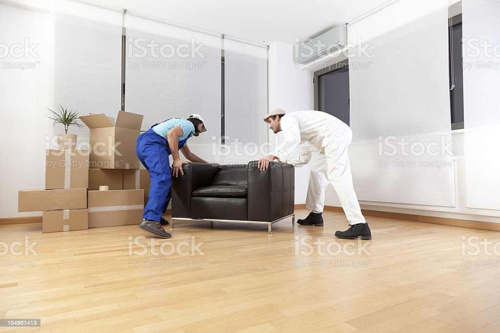 Couple of workers moving the furniture into a new house royalty-free stock photo