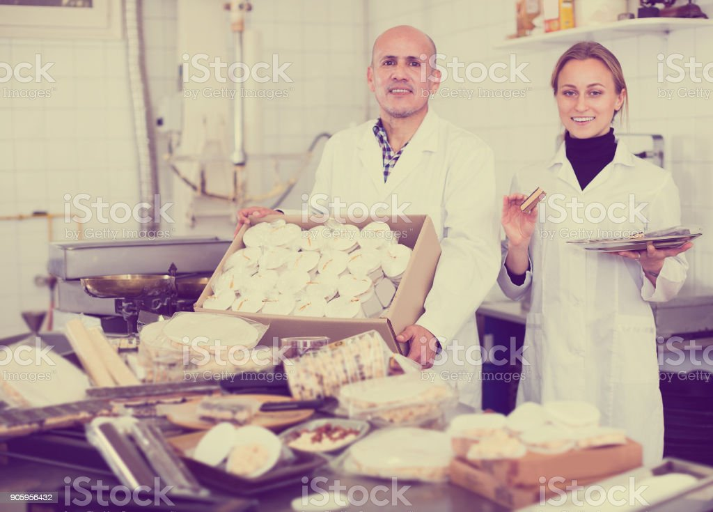 Couple of workers standing with box of turron stock photo