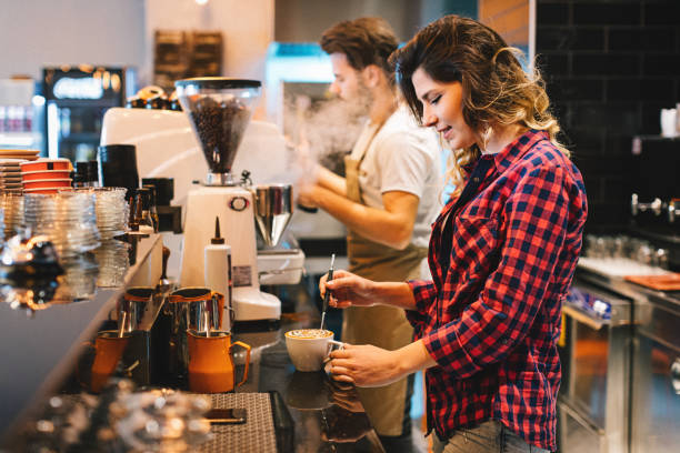 Couple of young baristas working together in a coffee shop stock photo