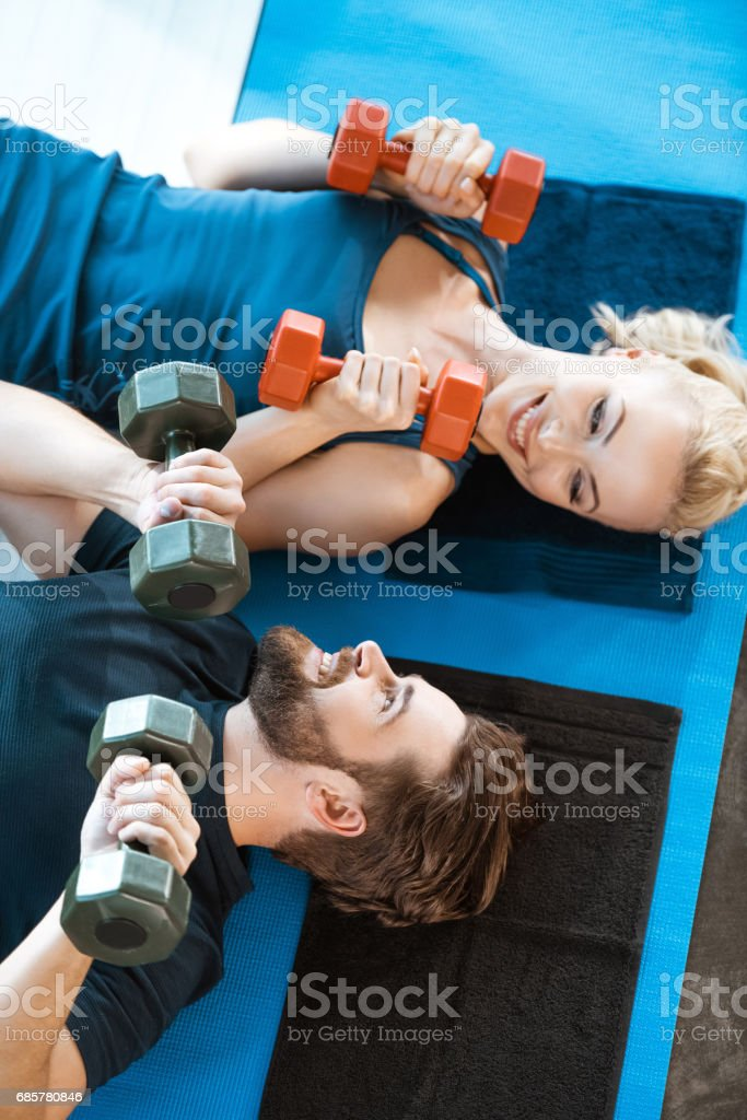 Couple of young fitness people exercising with dumbbells at fitness studio photo libre de droits