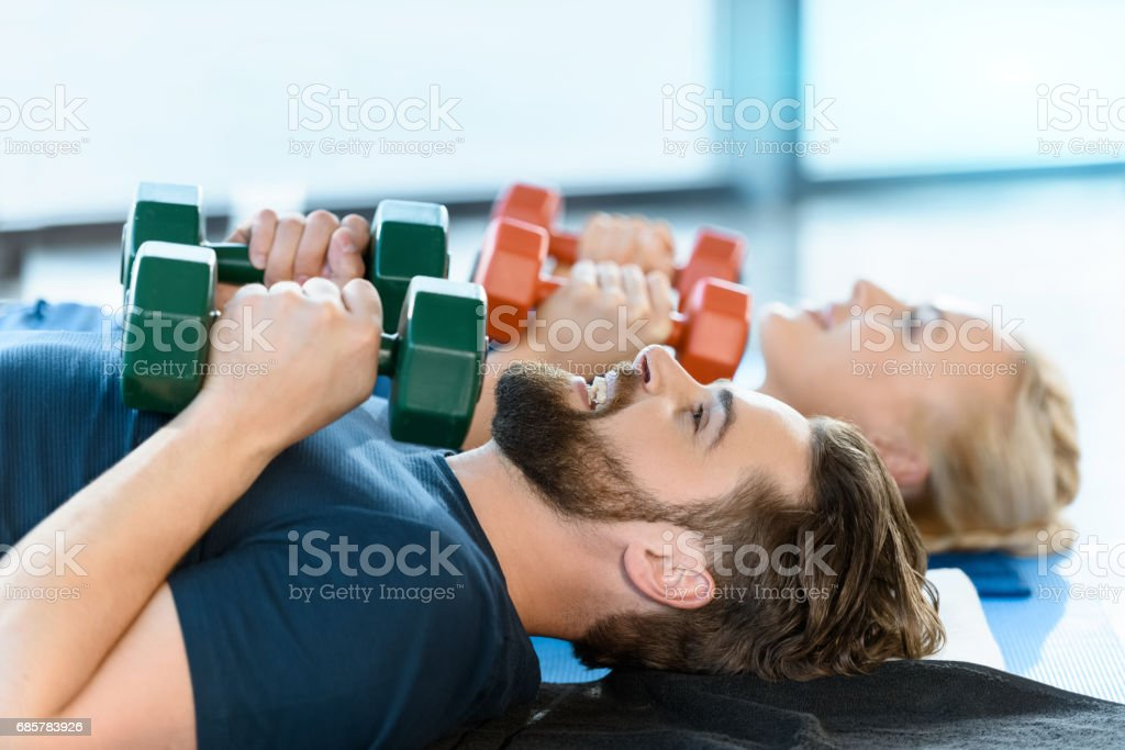 Couple of young fitness people exercising with dumbbells at fitness studio royalty-free stock photo