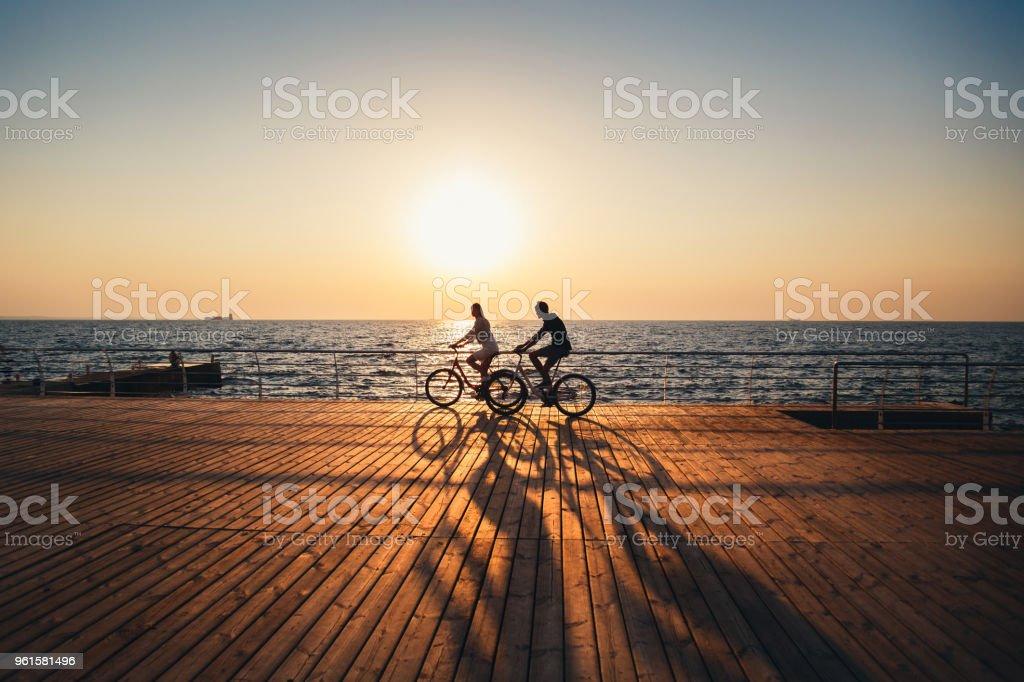 一對年輕的嬉皮士騎自行車一起在海灘上日出天空在木甲板夏季時間 - 免版稅一起圖庫照片