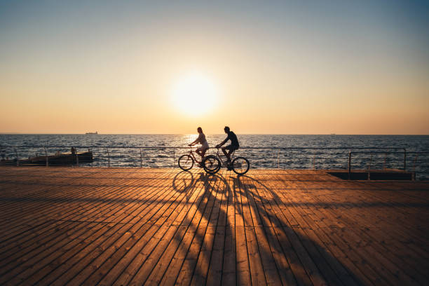 Couple of young hipsters cycling together at the beach at sunrise sky at wooden deck summer time stock photo