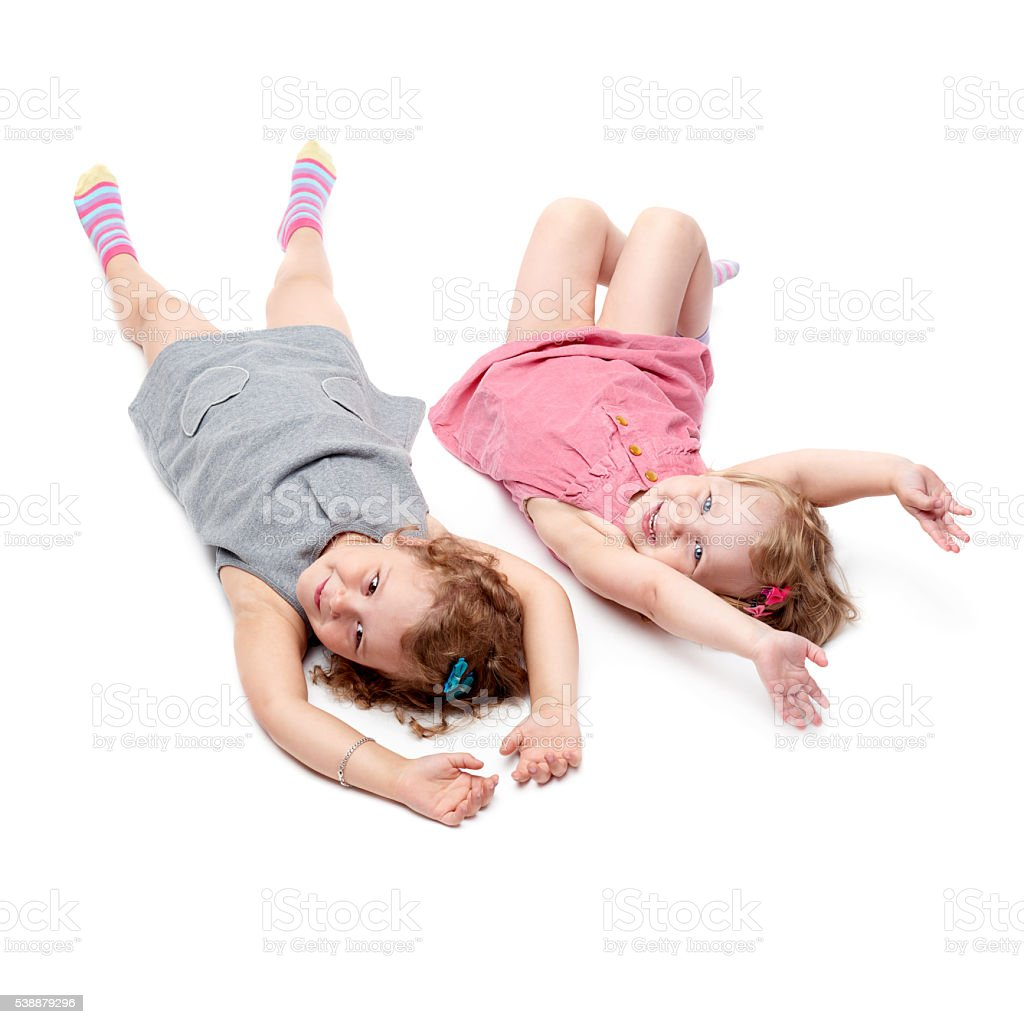 962a0fbc64b1 Couple Of Young Little Girls Lying Over Isolated White Background ...