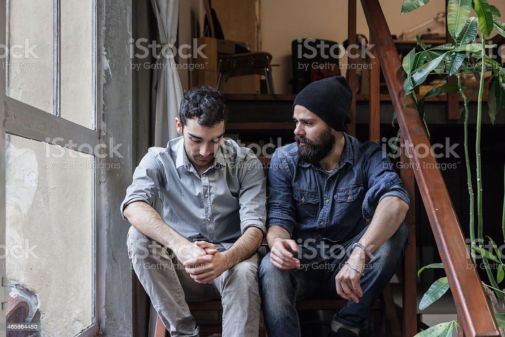 Couple of young men talking on the stairs stock photo