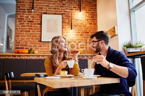 Couple of young people drinking coffee and eating cake in a stylish modern cafeteria