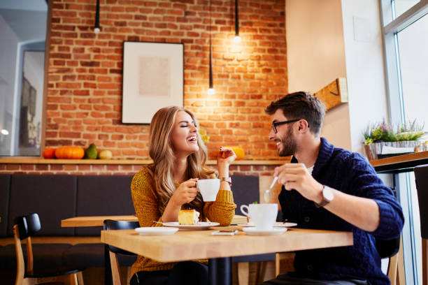Couple of young people drinking coffee and eating cake in a stylish modern cafeteria Couple of young people drinking coffee and eating cake in a stylish modern cafeteria romantic activity stock pictures, royalty-free photos & images