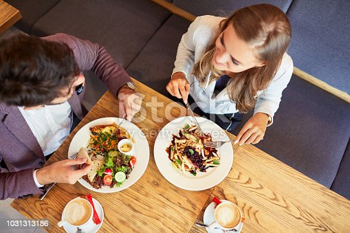 istock Couple of young people eating breakfast together while sitting in restaurant and smiling 1031313186