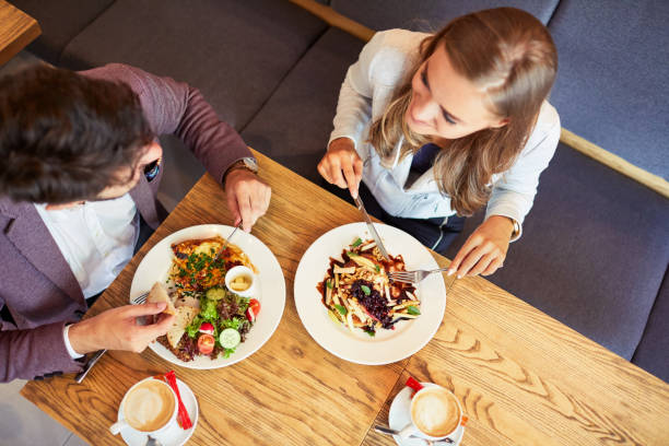 Couple of young people eating breakfast together while sitting in restaurant and smiling stock photo