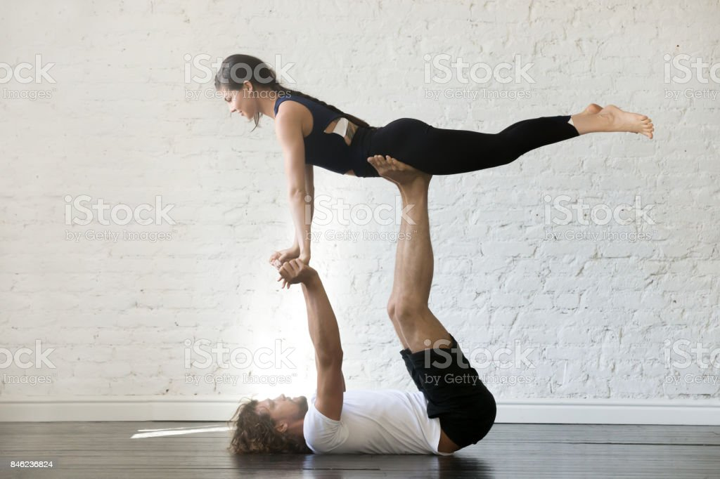Couple of young sporty people practicing yoga stock photo