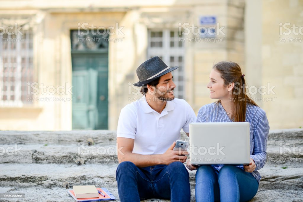 couple of young students man and woman working together with a laptop computer outdoor in a street during summer zbiór zdjęć royalty-free