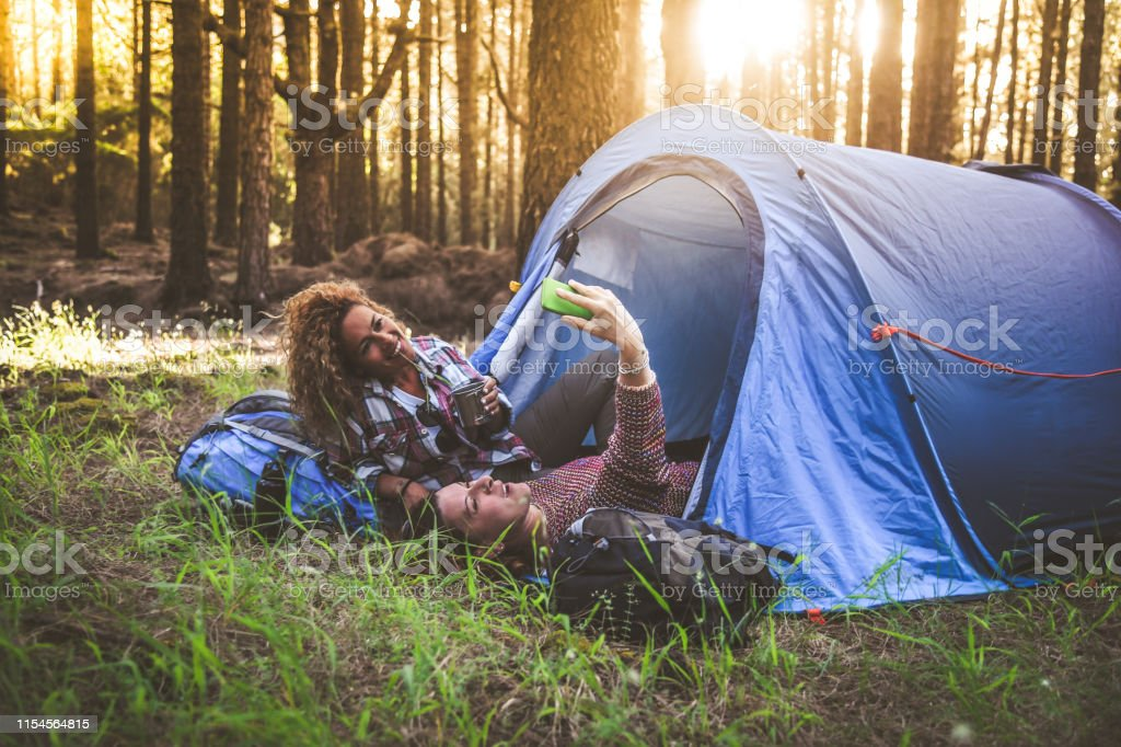 Couple of young trendy women making social video story in a camping...