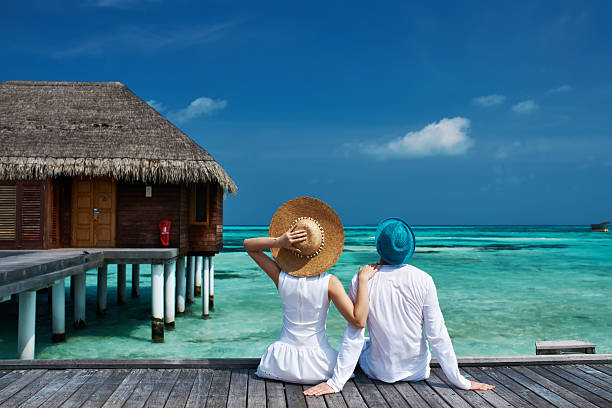Couple on a beach jetty at Maldives Couple on a tropical beach jetty at Maldives bungalow stock pictures, royalty-free photos & images