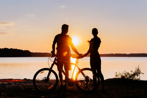 couple on a bicycle at sunset by the lake couple on a bicycle at sunset by the lake. female biker resting stock pictures, royalty-free photos & images