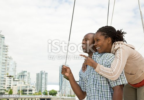 istock Couple on a Boat Pointing at City Skyline 523186429
