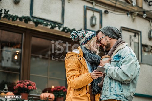 Young couple is on a city tour, dressed in warm clothes. Girl is holding smart phone
