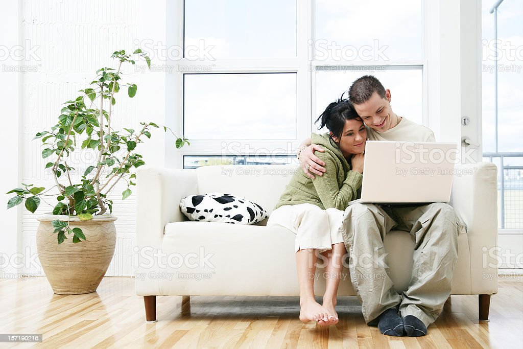 Couple on a couch, browsing royalty-free stock photo