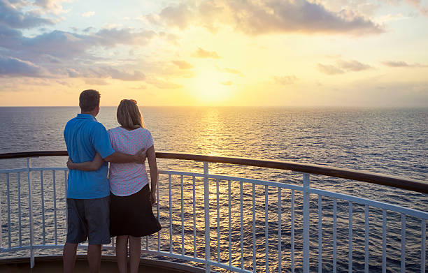 Couple on a cruise watching the sunset over the ocean stock photo