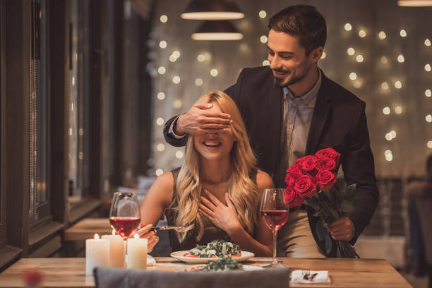 A man surprising his girlfriend with romantic dinner date https://www.istockphoto.com/photos/dinner-date