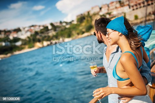 Closeup side view of a young couple relaxing on a sailboat cruise while sailing close to the coast. They are having some wine.