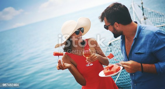 Closeup side view of a young couple relaxing on a sailboat cruise while sailing close to the coast. They are having some wine and watermelon.