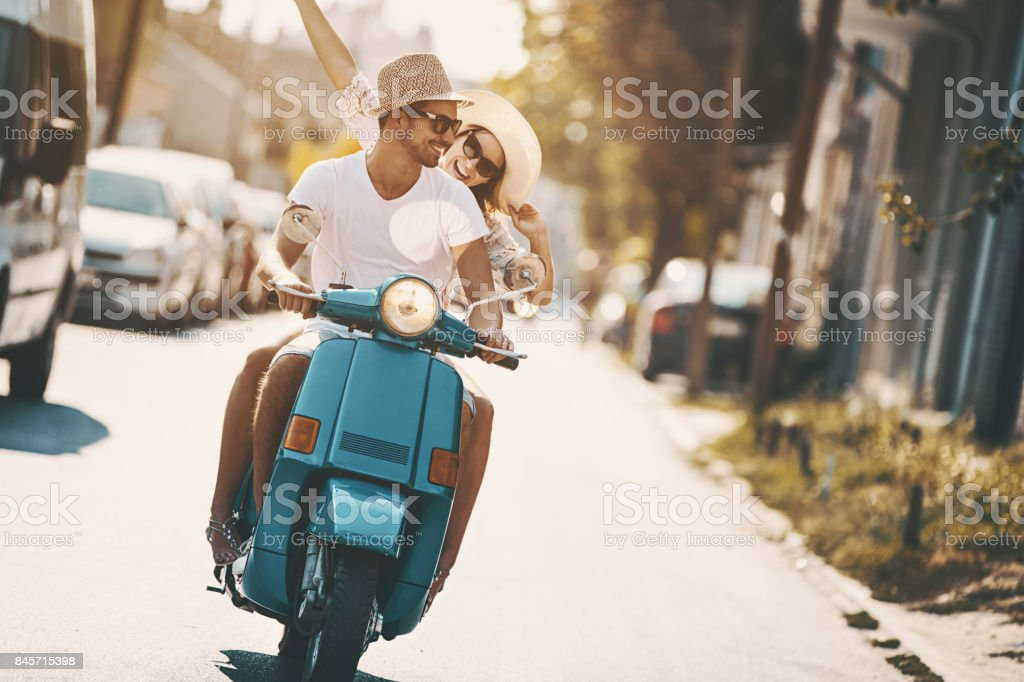 Closeup front view of mid 20\'s couple cruising on a blue scooter bike...