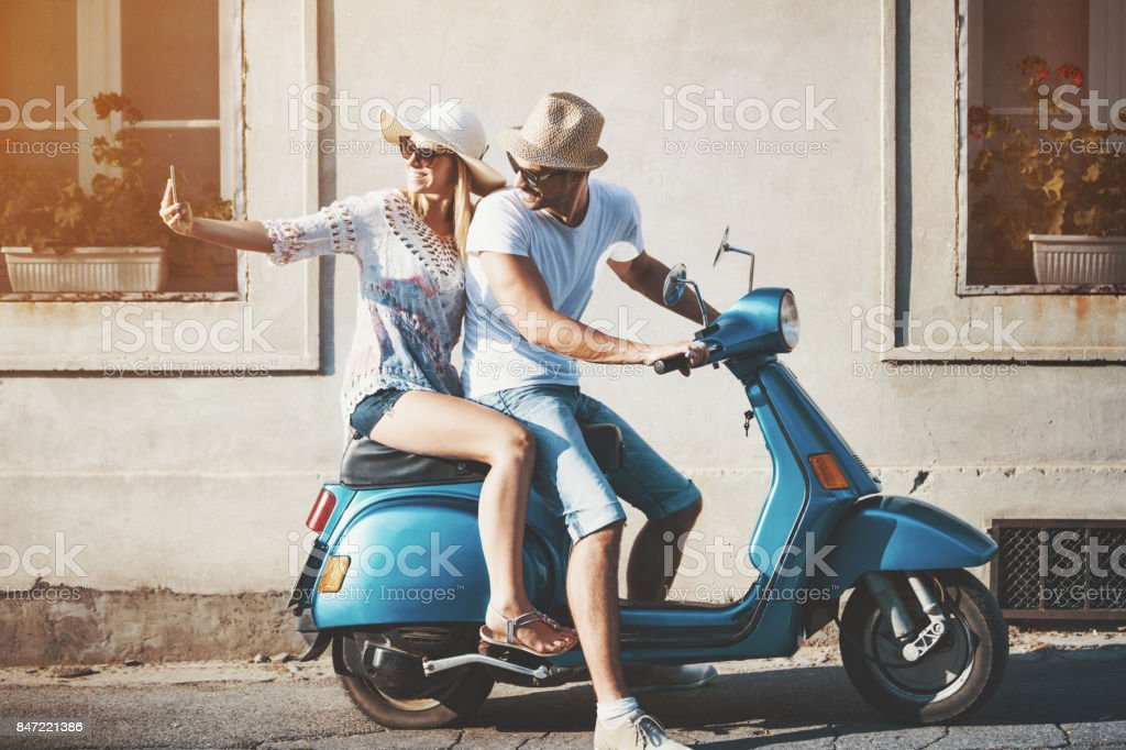 Closeup side view of mid 20\'s couple cruising a scooter bike on a...