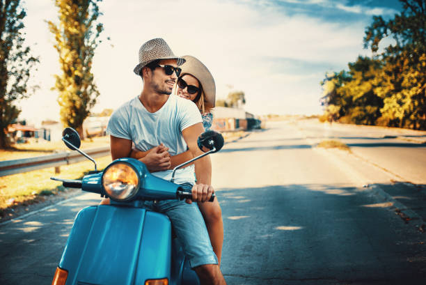 Couple on a scooter bike driving through city streets. stock photo