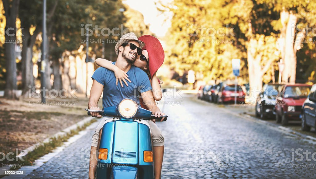 Closeup front view of mid 20\'s couple cruising a scooter bike on a...