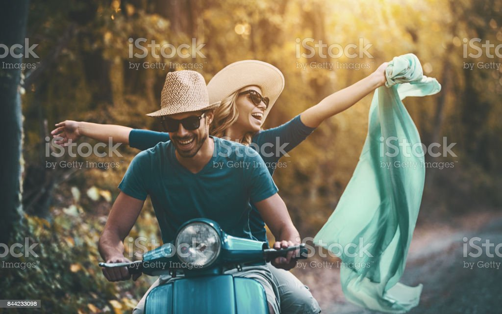 Couple on a scooter bike driving through countryside. stock photo