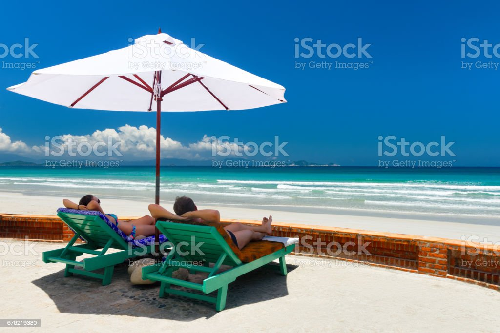 Couple on a tropical beach on deck chairs under a white umbrella. stock photo