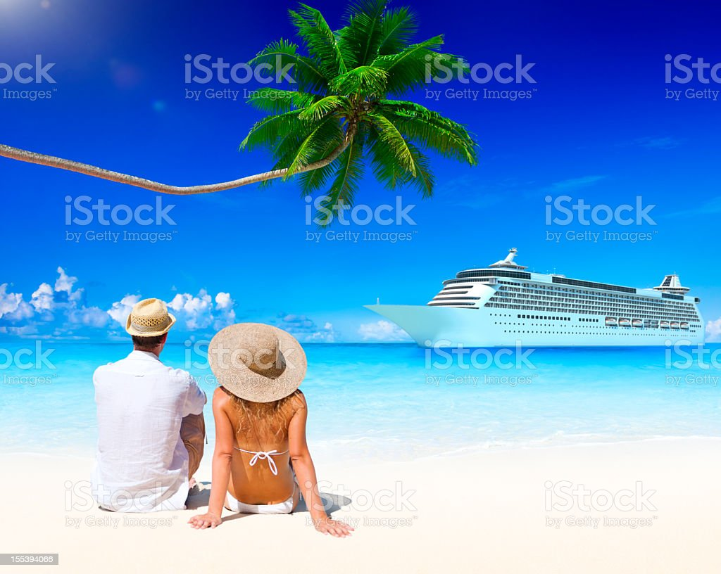A couple on a tropical beach with a cruise ship in the water stock photo