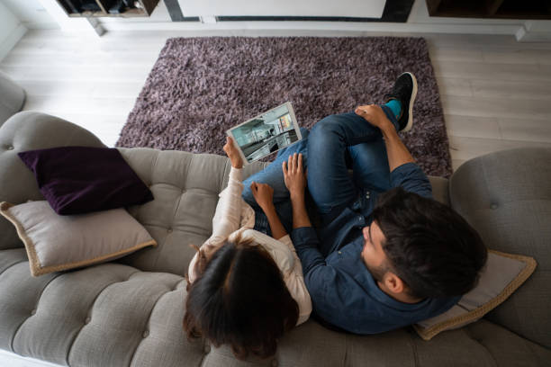 Couple on a video call with their realtor and taking a virtual tour of a house for sale stock photo